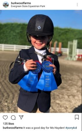 Young girl showing off ribbons in the Equestrian park